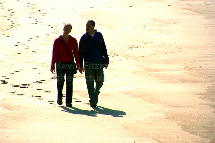 COUPLE HOLDING HANDS WALKING ALONG A BEACH