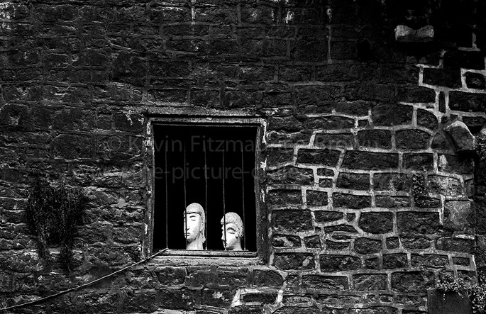 TWO STONE HEADS IN A WINDOW