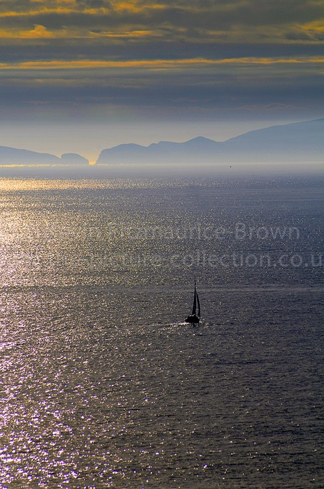A YACHT SAILS IN STANGE COLOURS, WALES